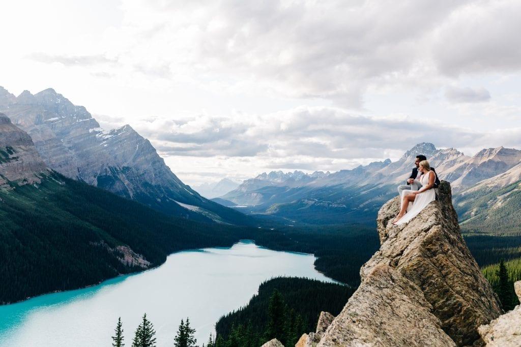 Couple sitting on rock ovelooking Peyto Lake, Banff National Park