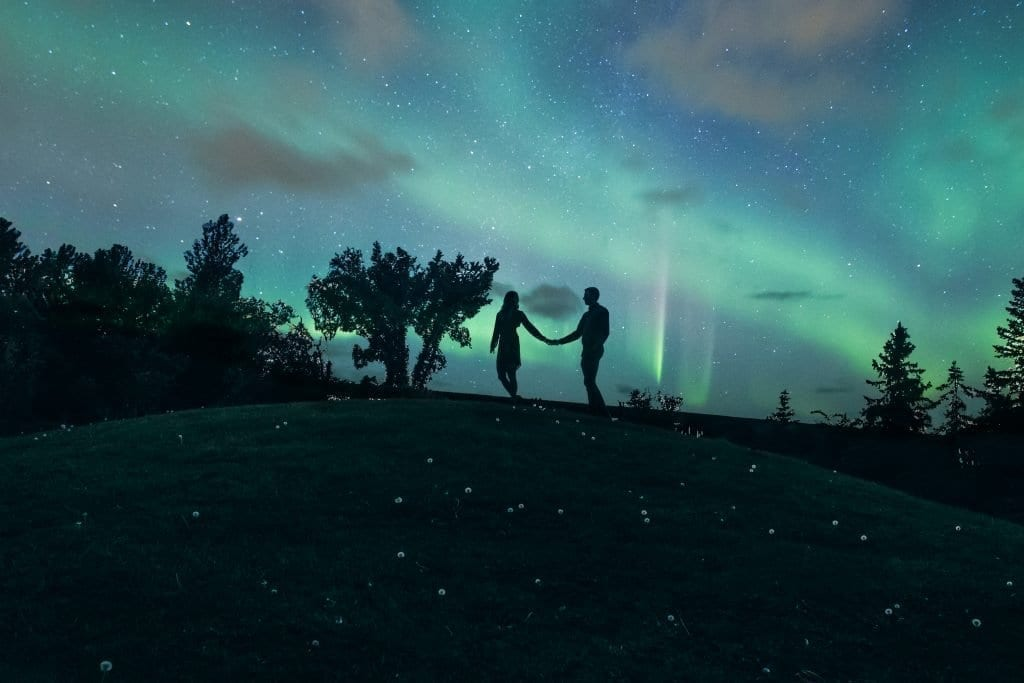 Night time photo of engaged couple in Iceland with the northern lights