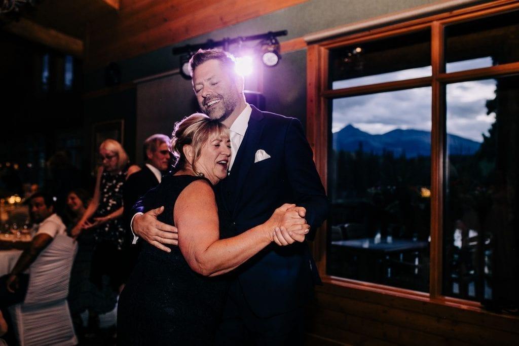 Happy mother of the groom dancing with his son photos