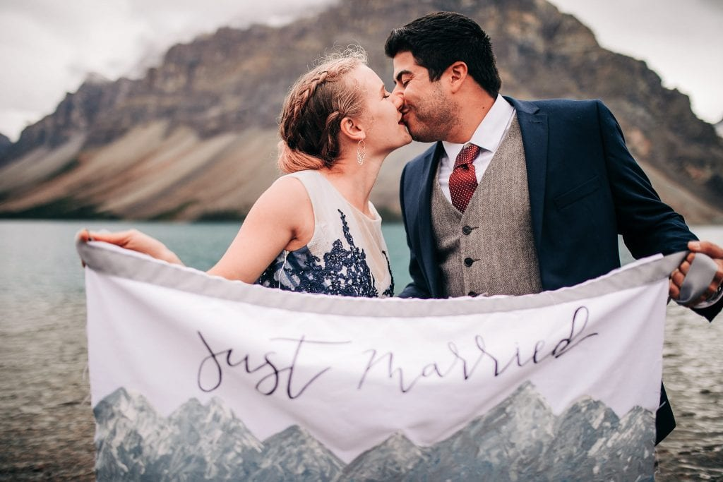newly eloped adventure couple kissing and holds just married sign